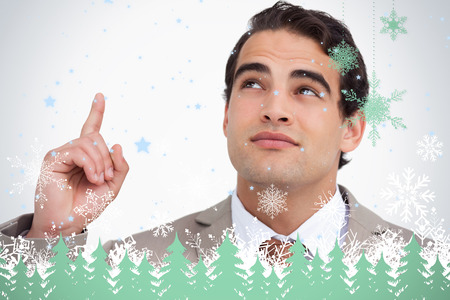 Close up of salesman looking and pointing up against snowflakes and fir trees in green photo