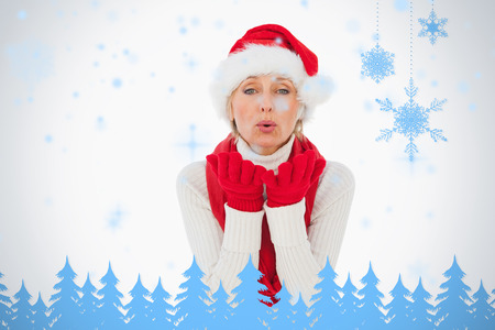 Festive woman blowing a kiss against snowflakes and fir trees in blue photo
