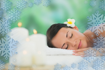 Beautiful brunette relaxing on massage table  against snowflake frame photo