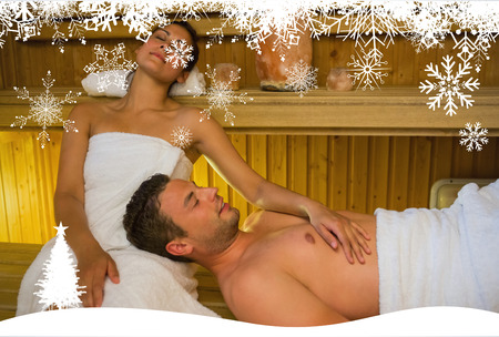 lap of luxury: Loving couple relaxing in a sauna against fir tree forest and snowflakes