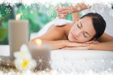 beauty wellness: Mooie brunette geniet van een kruiden kompres massage tegen sparrenbos en sneeuwvlokken Stockfoto