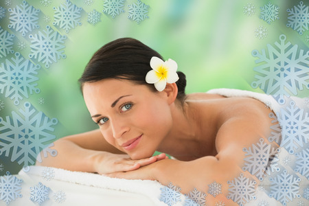 Beautiful brunette relaxing on massage table smiling at camera against snowflake frame photo