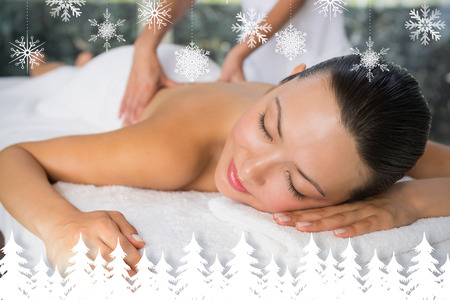 spa treatment: Content brunette enjoying a back massage  against fir tree forest and snowflakes Stock Photo