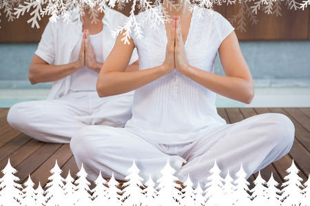 Couple in white sitting in lotus pose with hands together against fir tree forest and snowflakes Stock Photo