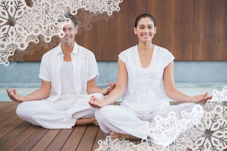 Attractive couple in white sitting in lotus pose smiling at camera against snowflake frame photo