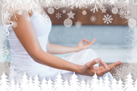 Peaceful woman in white sitting in lotus pose  against fir tree forest and snowflakes Foto de archivo