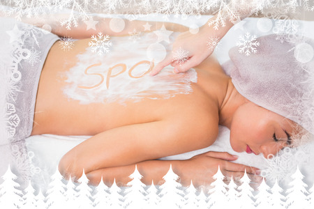 Attractive woman receiving back mask cream at spa center against fir tree forest and snowflakes photo