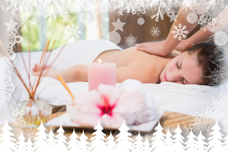 Attractive woman receiving back massage at spa center against fir tree forest and snowflakes photo