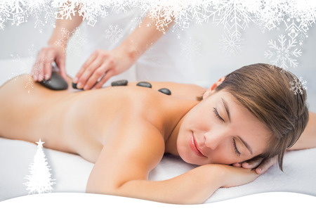 Beautiful woman receiving stone massage at spa center against fir tree forest and snowflakes photo