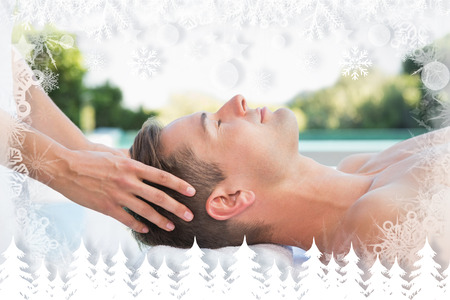 Peaceful man getting a head massage poolside against fir tree forest and snowflakes photo