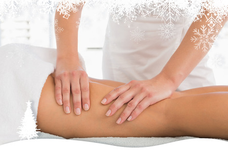 Close-up of a woman receiving leg massage against fir tree forest and snowflakes photo