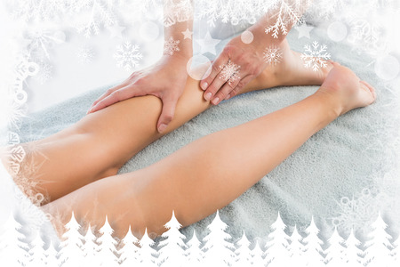 Woman receiving leg massage at spa center against fir tree forest and snowflakes photo