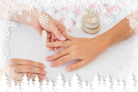 Nail technician filing customers nails against fir tree forest and snowflakes photo