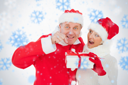 Festive couple smiling and holding gift against snowflakes photo