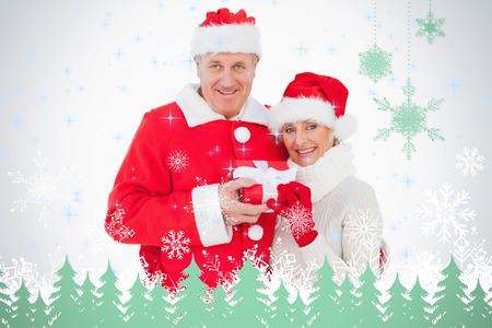 Festive couple smiling and holding gift against snowflakes and fir trees in green photo