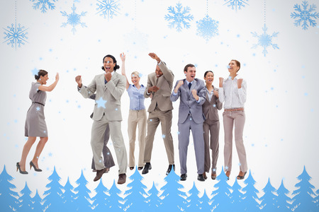 Very happy business people jumping and clenching their fists against snowflakes and fir trees in blue photo