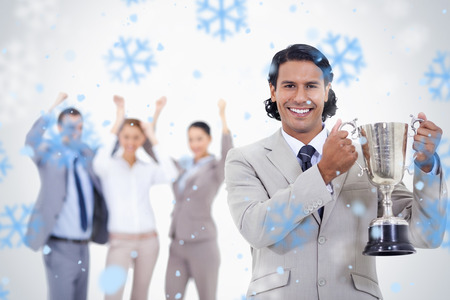 awarded: Close up of a man dressed in a suit smiling and holding a cup with people cheering behind him against snowflakes