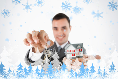 residential tree service: Close up of keys and miniature house being held by male estate agent against snowflakes and fir trees