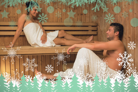 Happy couple relaxing in a sauna and chatting against snowflakes and fir trees in green photo