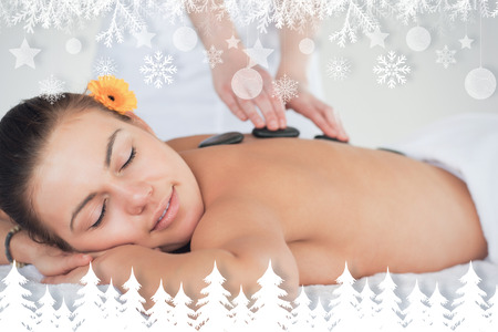 Close up of a woman enjoying a hot stone massage against fir tree forest and snowflakes photo