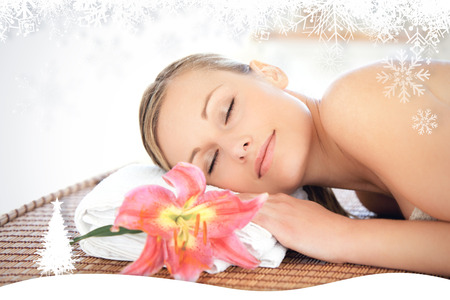 Portrait of a cute woman having a massage  against fir tree forest and snowflakes photo