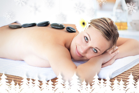 Glowing young woman with hot stone on her back smiling at the camera against fir tree forest and snowflakes photo