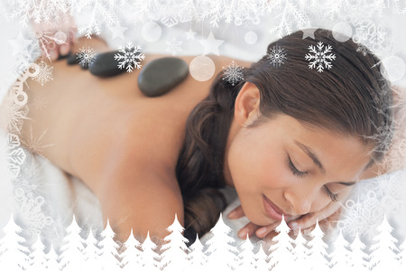 hot stone massage: Beautiful brunette enjoying a hot stone massage against fir tree forest and snowflakes