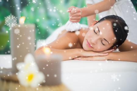 Beautiful brunette enjoying a herbal compress massage against snow falling photo