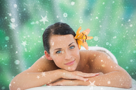 Beautiful brunette relaxing on massage table smiling at camera against snow photo
