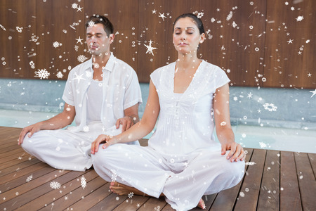 Attractive couple in white sitting in lotus pose against snow falling photo
