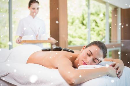 Beautiful woman receiving stone massage at health farm against snow falling photo