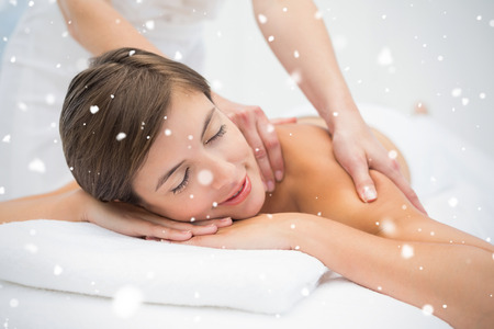 Attractive young woman receiving shoulder massage at spa center against snow falling photo