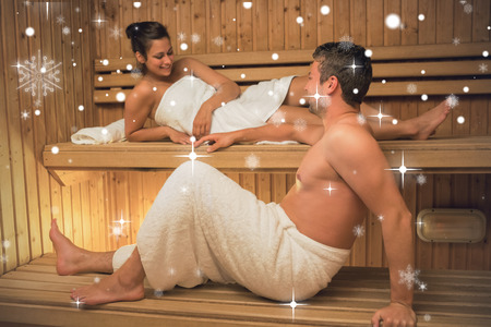 Calm couple relaxing in a sauna and chatting against snow falling photo