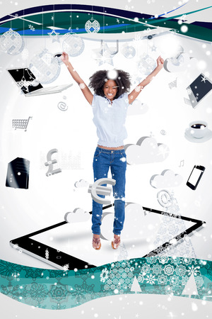 Composite image of a Cheerful woman jumping on a tablet pc against snow falling photo