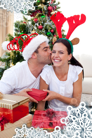 Smiling couple giving presents for Christmas against snowflake frame photo