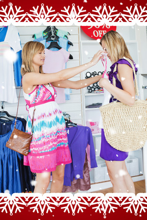 choosing clothes: Cheerful women choosing clothes together against snow falling Stock Photo