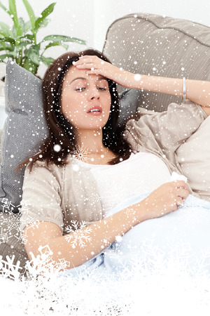 Sick woman lying on the sofa and touching her forehead  against snow falling photo