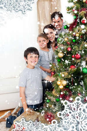 Happy family decorating a Christmas tree with boubles and presents against snow falling photo