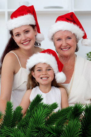 Daughter mother and grandmother baking Christmas sweets against digitally generated fir tree branches photo