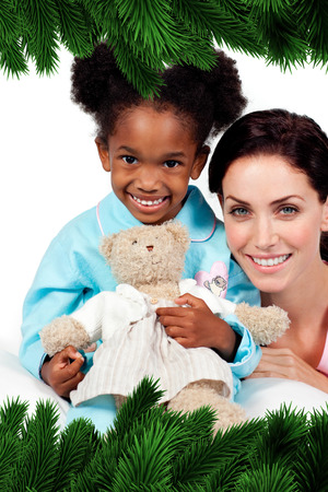 Smiling little girl with her nurse looking at the camera  against fir tree branches forming frame photo