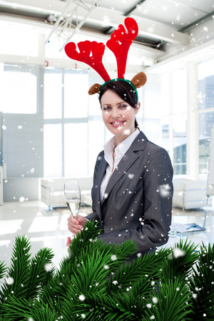 Composite image of a Smiling businesswoman with a novelty Christmas hat drinking Champagne  against snow falling photo