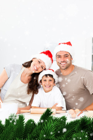 Composite image of a Happy family baking christmas cookies together against snow falling photo
