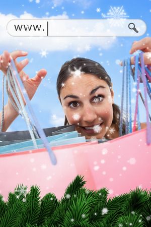 address bar: Composite image of a Woman holding up her shopping bags under address bar against snow falling Stock Photo