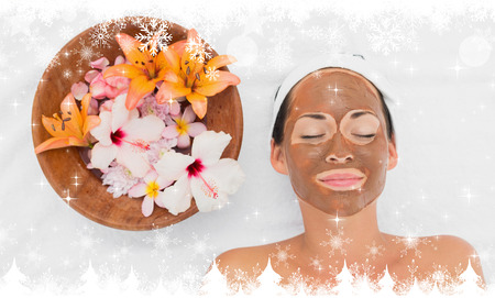 mud and snow: Composite image of a Smiling brunette getting a mud treatment facial beside bowl of flowers against snow Stock Photo