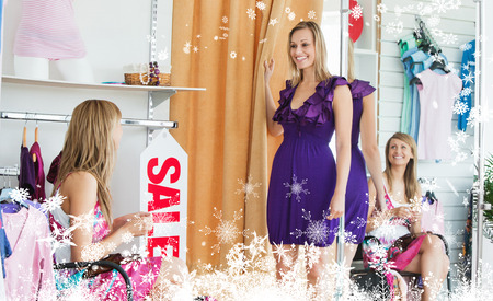 Composite image of a Delighted women choosing clothes together against snow photo
