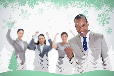 Successful business team with a man in the foreground against snowflakes and fir tree in green photo