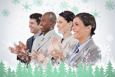 upright row: Side view of clapping sales team standing together against snowflakes and fir trees in green