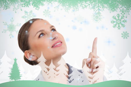 Close up of tradeswoman looking and pointing up against snowflakes and fir tree in green photo