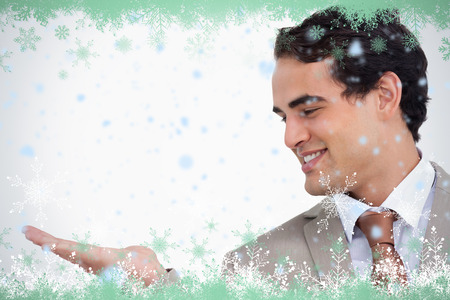 Close up of smiling salesman looking at his palm against snow flake frame in green photo