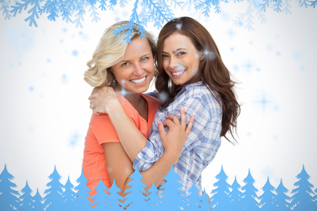 Two friends taking each other in arms against frost and fir trees in blue photo